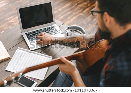 Young guitarist hipster at home holding guitar using laptop #1011078367