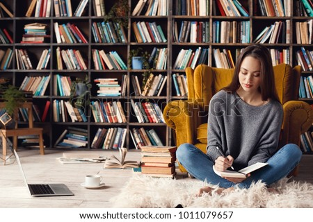 Young woman writer in library at home creative occupation sitting writing notes #1011079657
