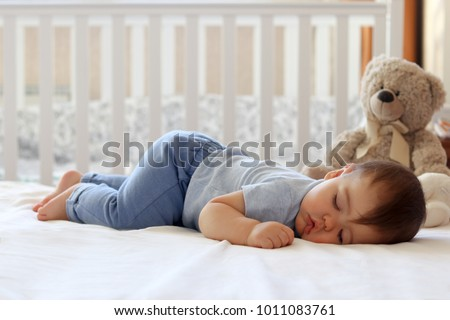 Funny baby sleeping on his stomach on bed at home. Child daytime bottom up sleeping position #1011083761