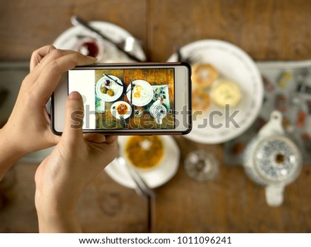 Take food photo before eating on the table share social media in restaurant and cafe and ignore friend