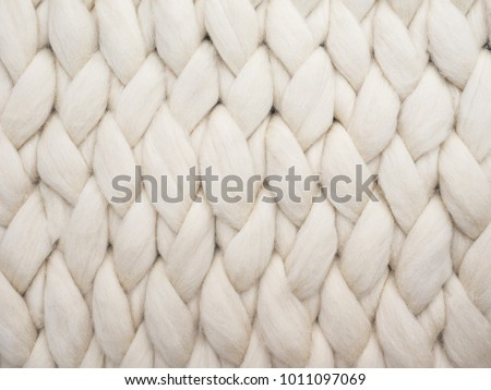 Merino wool handmade knitted large blanket, super chunky yarn, trendy concept. Close-up of knitted blanket, merino wool background #1011097069