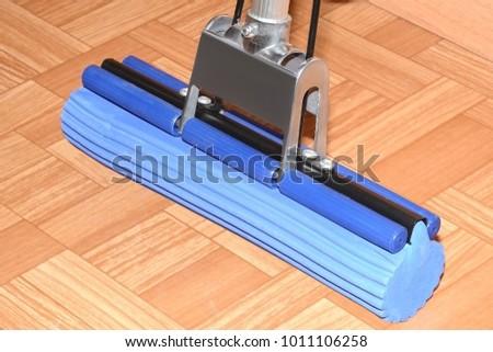Blue MOP with sponge is on the floor on linoleum #1011106258