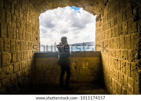 Tourist young girl sitting above the adriatic sea at the ruins of a fortress window #1011174157