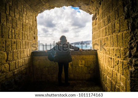 Tourist young girl sitting above the adriatic sea at the ruins of a fortress window #1011174163