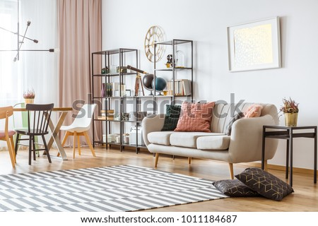 Painting on white wall above sofa with cushions in living room interior with chairs at the table under metal lamp #1011184687