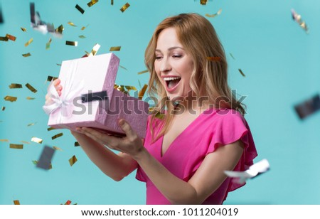 What is inside. Curious young woman is looking into present box and laughing with happiness. Holiday celebration concept Royalty-Free Stock Photo #1011204019