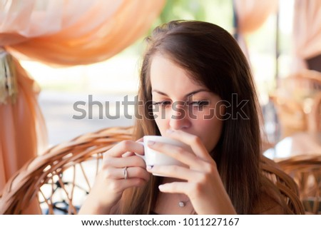Close-up portrait of a beautiful woman with a cup of coffee at a cafe #1011227167