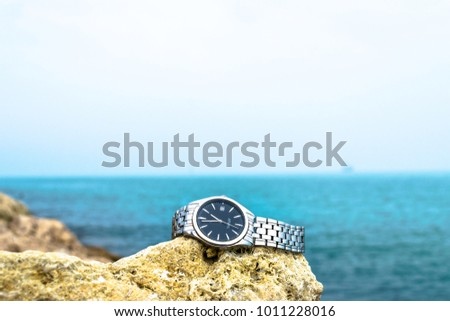 an exotic stainless silver watch kept on the brownish rocks at the beach and greenish sea water in the background cloudy day  Royalty-Free Stock Photo #1011228016