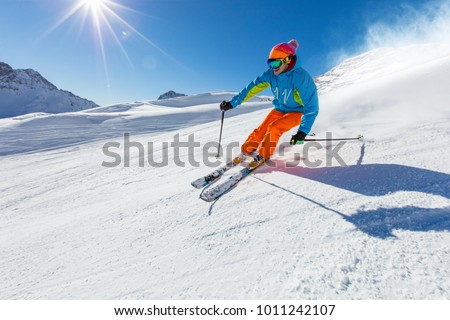 Skier skiing downhill during sunny day in high mountains #1011242107