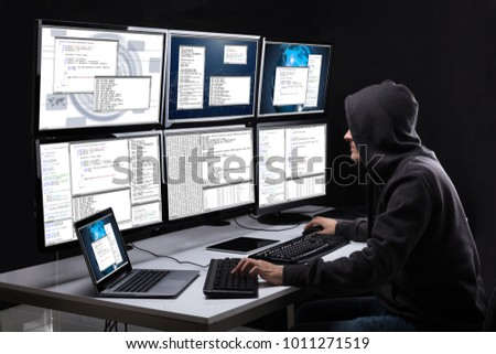 Rear View Of A Hacker Using Multiple Computers For Stealing Data In Office #1011271519