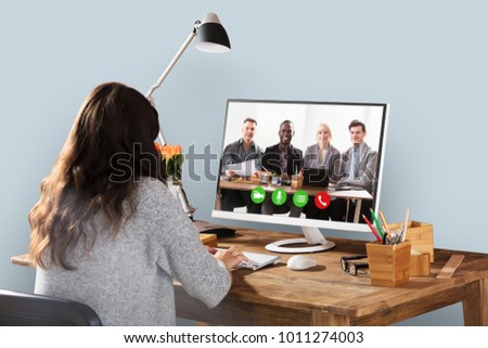 Woman Video Conferencing With Smiling Male And Female Colleagues On Computer #1011274003