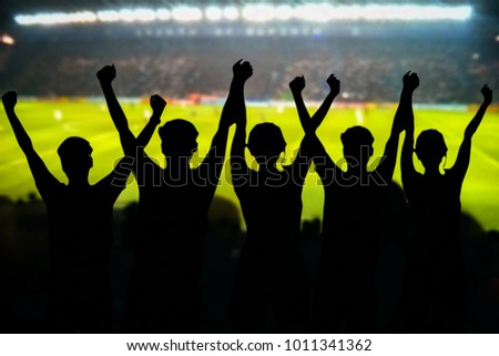 silhouettes of Soccer fans in a match and Spectators at football stadium #1011341362