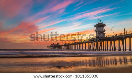 Incredible colors of sunset by Huntington Beach Pier, in the famous surf city in California Royalty-Free Stock Photo #1011355030