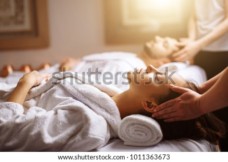 Young couple receiving head massage at beauty spa #1011363673