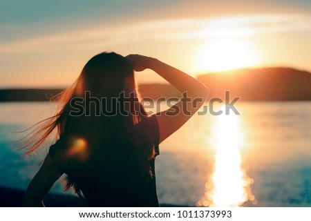 Happy Hopeful Woman Looking at the Sunset by the Sea. Silhouette of a dreamer girl looking hopeful at the horizon  Royalty-Free Stock Photo #1011373993