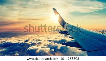 flying and traveling, view from airplane window on the wing on sunset time #1011385708