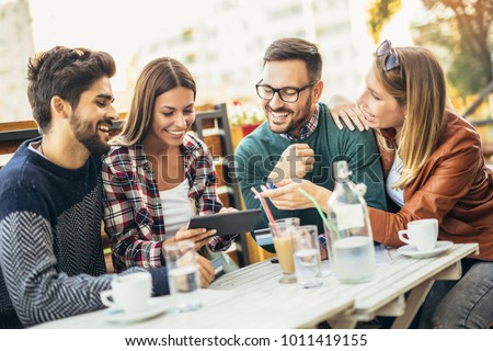 Group of four friends having fun a coffee together. Two women and two men at cafe talking laughing and enjoying their time #1011419155