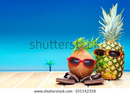 Two fruity friends, a coconut and pineapple, with fun foliage haistyles and trendy sunglasses in tropical paradise