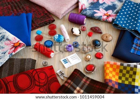 Fabric and objects for sewing. Multicolored cloths are scattered on the table. Buttons, a set of needles, thread reels are needed for sewing clothes from fabric. Fabrics of different types for sewing. #1011459004