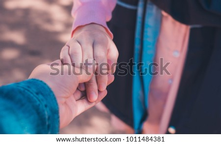 A young man holding hands with a girl shows love that he loves her. #1011484381