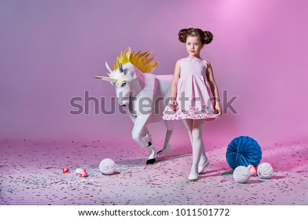 Romantic little girl in beautiful pink dress. Origami and minimalism. Fashion children. Designer collection. White big unicorn origami made of paper. #1011501772