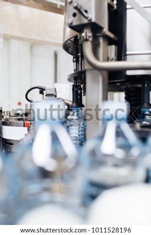 Bottling plant - Water bottling line for processing and bottling pure spring water into blue bottles. Selective focus.  #1011528196