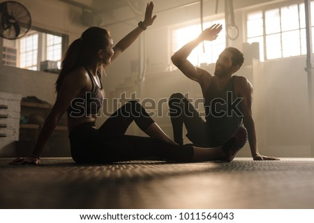 Fitness man and woman giving each other a high five after the training session in gym. Fit couple high five after workout in health club. Royalty-Free Stock Photo #1011564043