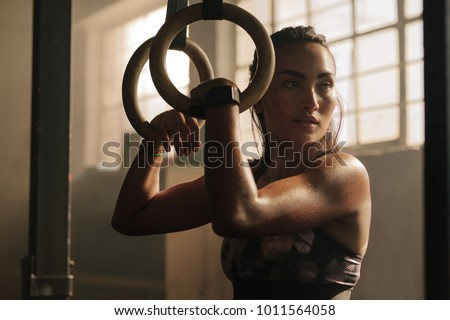 Exercising woman holding gymnast rings and looking away. Female taking rest after intense dip ring workout at gym. #1011564058