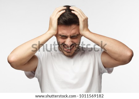 Upset unhappy young man in white t-shirt squeezing head with hands, suffering from headache. People, stress, tension and migraine concept #1011569182