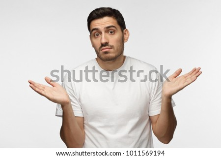 I don't know. Young man isolated on grey background being at a loss, showing helpless gesture with arm and hands, mouth curved as if he does not know what to do #1011569194