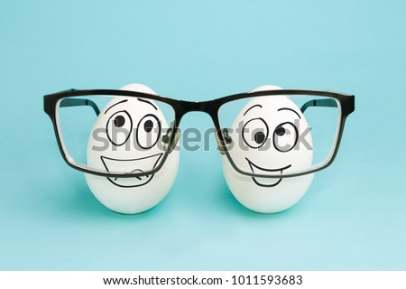 Two funny eggs look through lenses of glasses. Correction of vision