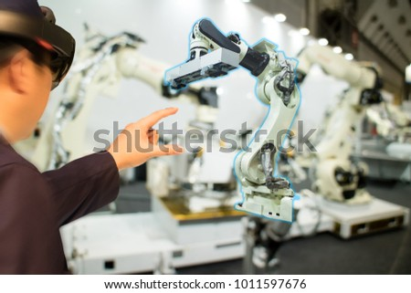 iot industry 4.0 concept,industrial engineer(blurred) using smart glasses with augmented mixed with virtual reality technology to monitoring machine in real time.Smart factory use Automation robot arm #1011597676