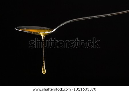 Honey dripping from a  spoon #1011633370