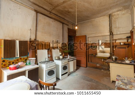 Dirty kitchen with furniture and gas stoves  is in the apartment for temporary  living (existence) refugees who were forced to migrate and emigrate from other countries. #1011655450
