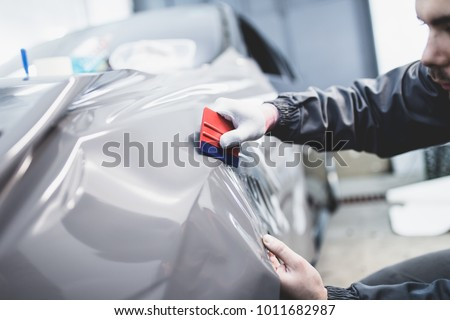 Car wrapping specialist putting vinyl foil or film on car. Royalty-Free Stock Photo #1011682987