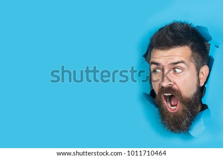 View of male face through hole in blue paper. Surprised bearded man making hole in paper. Cute attractive man looking through hole. Copy space for advertising, to insert text or slogan. Discount, sale #1011710464