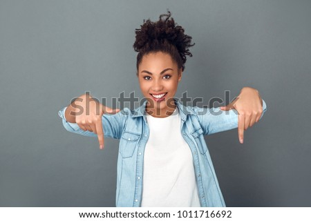 Young african woman isolated on grey wall studio casual daily lifestyle pointing down #1011716692