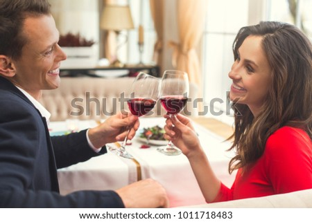 Young couple having romantic dinner in the restaurant sitting together holding wine glasses back view #1011718483