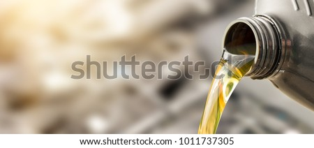 Pouring oil to car engine. Fresh oil poured during an oil change to a car. #1011737305