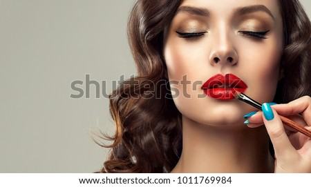 Makeup artist applies  red lipstick  . Beautiful woman face. Hand of make-up master, painting lips of young beauty  model girl . Make up in process Royalty-Free Stock Photo #1011769984
