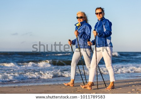 Nordic walking - active people working on beach #1011789583