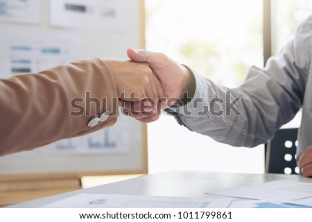 Business team two shaking hands after a meeting to sign agreement and become partner in the office, contract between their firms. #1011799861
