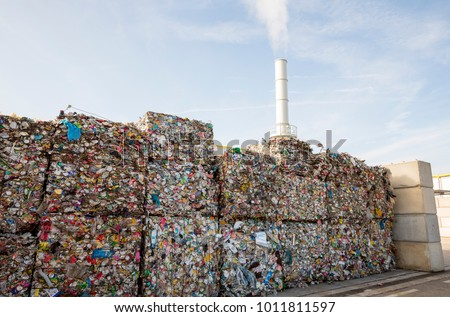 Waste-to-energy or energy-from-waste is the process of generating energy in the form of electricity or heat from the primary treatment of waste. Cubes of pressed metal beer and soda cans. #1011811597