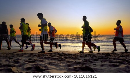Durres, Albania - circa August, 2017: Football sport team is engaged in jogging training at sea at sunset. They make a run along the sea coast. cinematic steadicam shot #1011816121