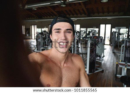 A boy during a break from training takes a picture in the gym to send to friends or girlfriend or to post on social networks. Concept of: sports, gym, photo and social network