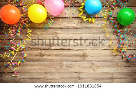 Colorful carnival or party frame of balloons, streamers and confetti on rustic wood planks with copy space