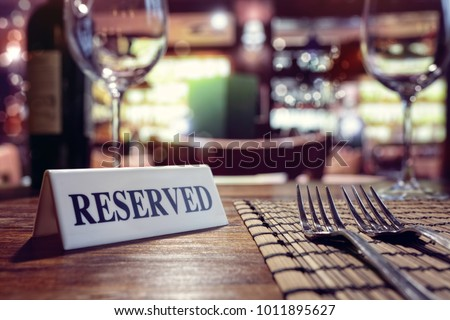 Restaurant reserved table sign with places setting and wine glasses ready for a party Royalty-Free Stock Photo #1011895627