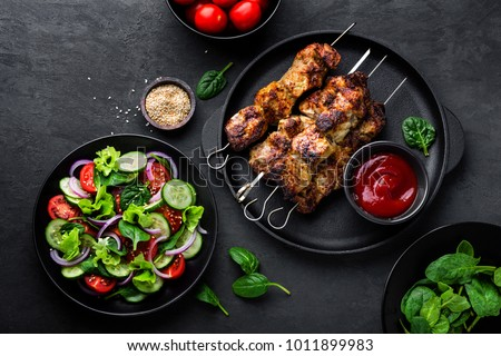 Grilled meat skewers, shish kebab and healthy vegetable salad of fresh tomato, cucumber, onion, spinach, lettuce and sesame on black background, top view #1011899983