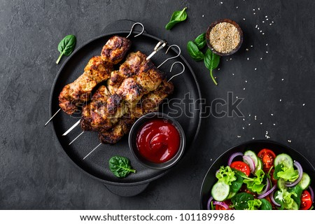 Grilled meat skewers, shish kebab and healthy vegetable salad of fresh tomato, cucumber, onion, spinach, lettuce and sesame on black background, top view #1011899986