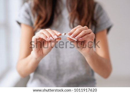 Stop smoking cigarettes concept. Portrait of beautiful smiling girl holding broken cigarette in hands. Happy female quitting smoking cigarettes. Quit bad habit, health care concept. No smoking. #1011917620
